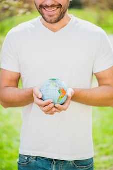 Close-up of smiling man holding globe in hand
