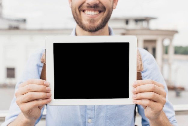 Close-up of smiling man showing digital tablet