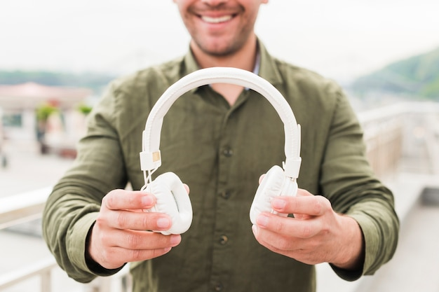 Close-up of smiling man showing white headphone