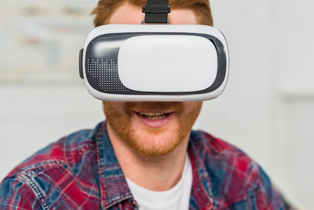 Close-up of a smiling man wearing virtual reality glasses