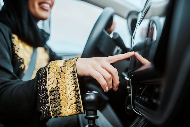 Close up of smiling muslim woman sitting in her new car and turning on gps. selective focus on hand.