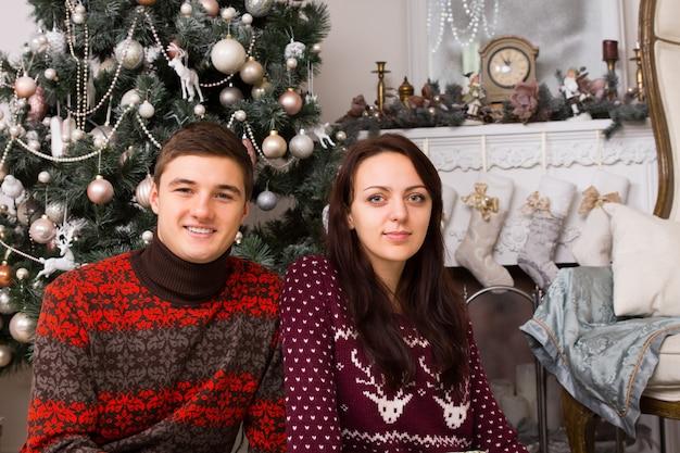 さまざまな装飾が施された魅力的なクリスマスツリーと煙突の壁の前でポーズをとっている笑顔のパートナーを閉じます。