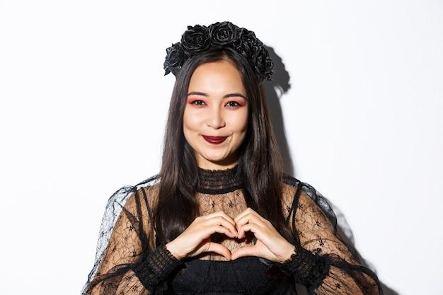 Primo piano di sorridente donna abbastanza asiatica in costume da strega e corona nera che mostra il gesto del cuore, amorevole vacanza di halloween, in piedi su sfondo bianco.