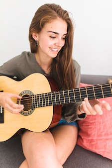 Close-up of a smiling teenage girl playing guitar at home