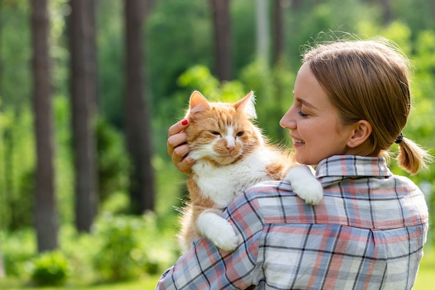 Close up of smiling woman in checked shirt hugging and embracing with tenderness and love domestic ginger cat, stroking on the head, outdoors in sunny day.
