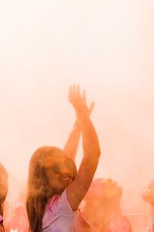 Primo piano di una donna sorridente che balla nel colore holi
