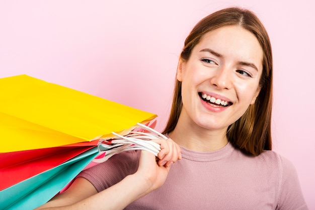Close-up smiling woman holding bags