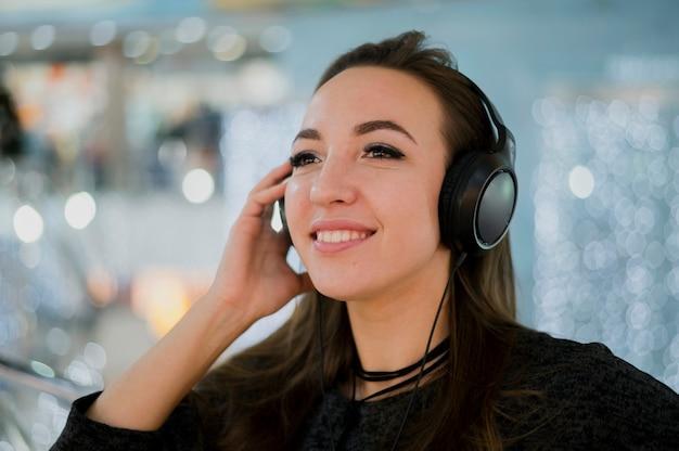 ショッピングモールの頭の上にヘッドフォンを保持しているクローズアップの笑顔の女性