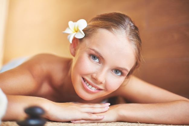 Close-up of smiling woman lying in spa