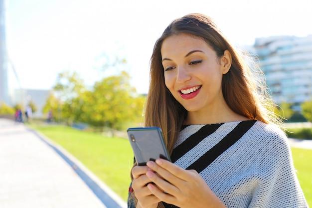 秋冬シーズンに屋外の携帯電話でメッセージング笑顔の女性を閉じます。
