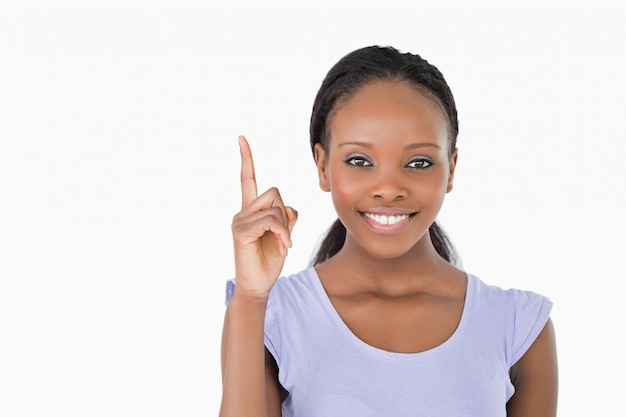 Close up of smiling woman pointing upwards on white background