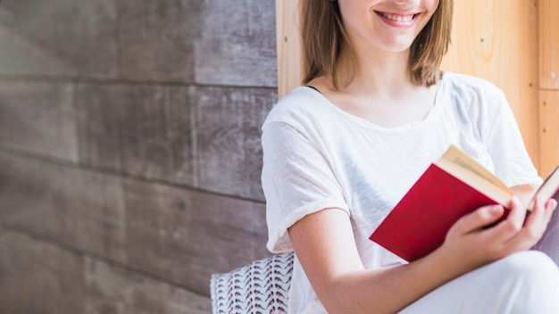 Close-up of smiling woman reading book