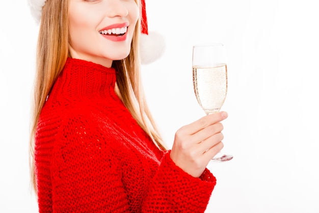Close up of smiling woman in red sweater holding glass of shampagne