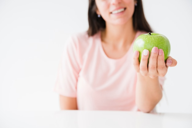 Close-up of a smiling woman showing green apple in hand against white backdrop
