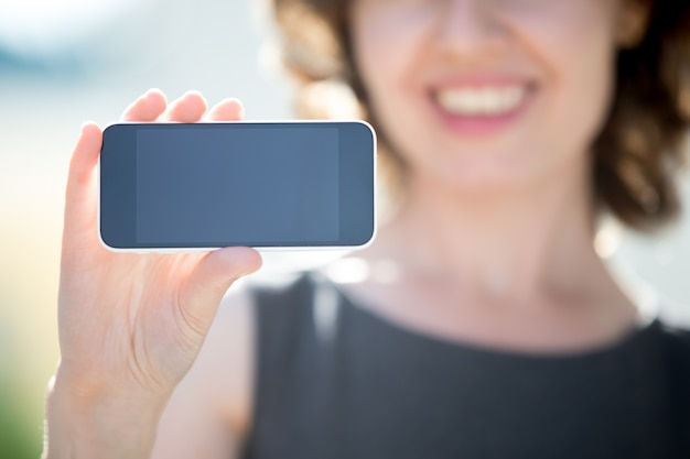 Close-up of smiling woman showing a mobile