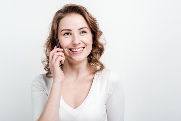 Крупным планом, улыбается женщина разговаривает по телефону.