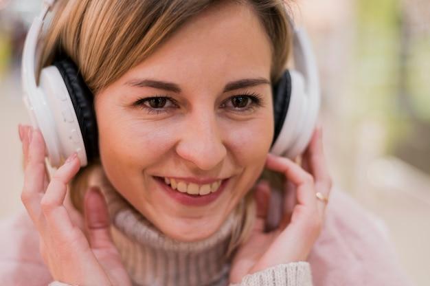 Макро улыбается женщина с heaphones в торговом центре