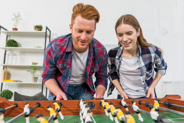 Close-up of smiling young couple playing the table soccer game at home