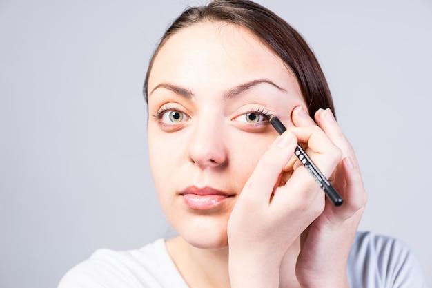 Закройте улыбающуюся молодую женщину, применяющую макияж подводки для глаз к левому глазу, глядя в камеру на сером фоне.