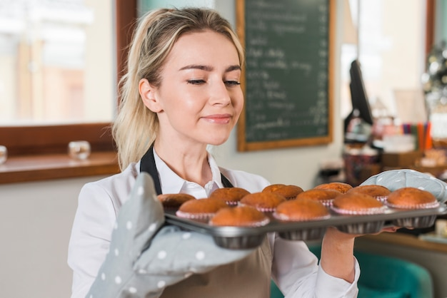 Close-up of smiling young woman enjoying the smells of baked muffins