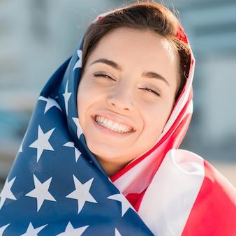 Макро улыбается молодая женщина, держащая большой флаг сша
