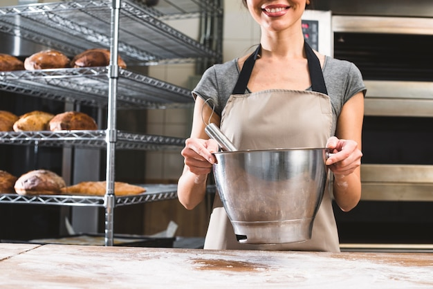 Close-up of smiling young woman holding mixing bowl at bakery