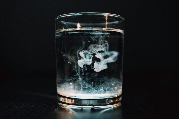 Close up on smoke effect in a glass of water