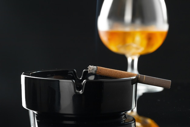Close up of smoking cigar and whiskey glass on table