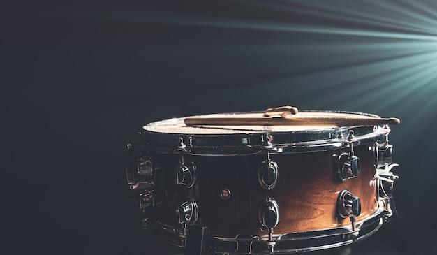 Primo piano di un rullante, strumento a percussione su uno sfondo scuro con una bella illuminazione, spazio di copia.