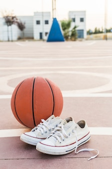 Close-up of sneakers and basketball in court