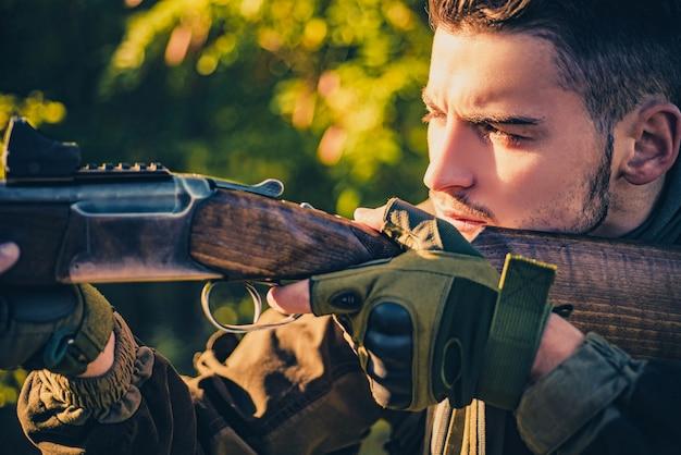 屋外の狩猟で狙撃兵のカービン銃をクローズアップ