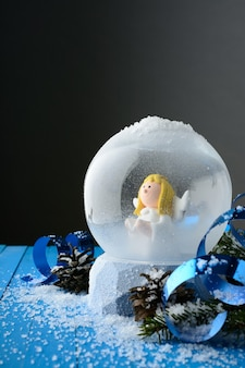 Close-up of snow globe with angel inside in composition with christmas decor on blue snowy surface.