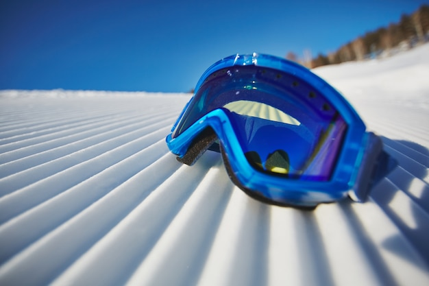 Close-up of snowboarding glasses on the snow