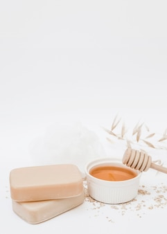 Close-up of soap; honey; honey dipper and loofah on white backdrop