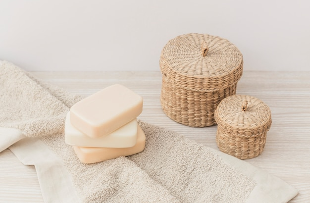 Close-up of soaps; towel and wicker basket on wooden surface