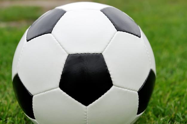 녹색 경기장 잔디에 축구 공을 닫습니다