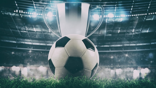 Close up of a soccer ball with trophy in the center of the stadium illuminated by the headlights