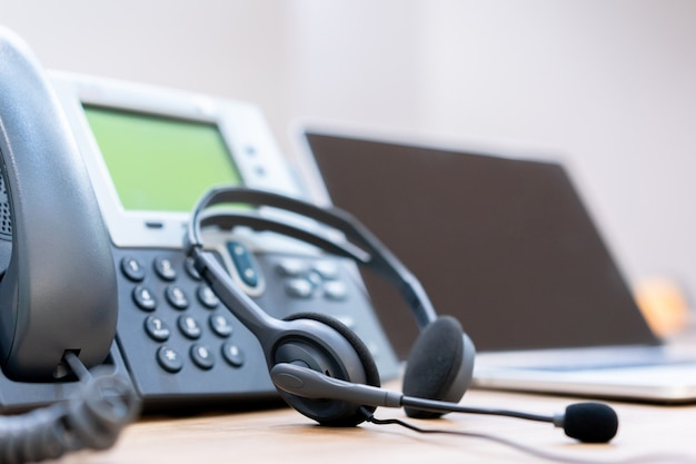 Close up soft focus on headset with telephone devices at office desk for customer service support