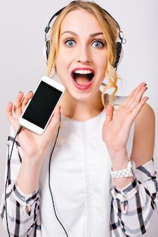 音楽を楽しんでいるとスマートフォンを楽しんで非常に美しい若い女性の柔らかい肖像画を閉じます。ポーズ。意気揚々。良い雰囲気。感情と感情。
