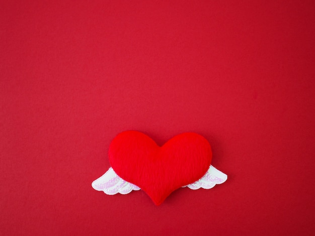 Close up soft red heart shape with two shiny white wings on red background.