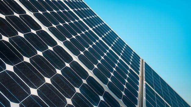 Закройте пластину солнечной энергии на фоне голубого неба