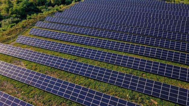 Закройте вверх панели солнечных электростанций подряд в полях зеленой энергии на закате