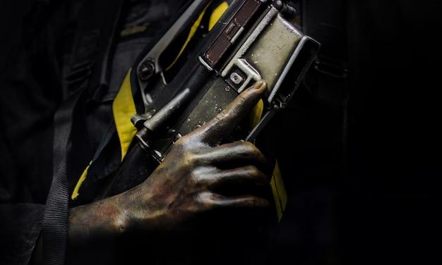 カモフラージュで兵士の手を閉じ、強さと戦争の概念で暗闇の中で銃のグリップをつかみます