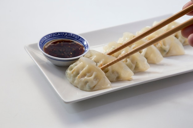 Close-up of some asian jiaozis or gyozas on a white ceramic plate and a blue ceramic bowl with soy sauce and sesame seeds.