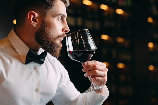 Close up of sommelier man sniffing wine in glass