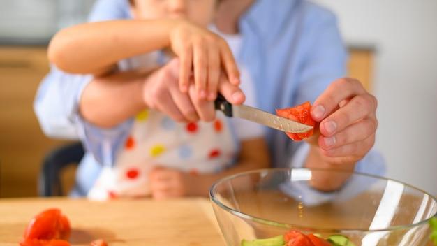 Крупным планом сын и папа режут помидор