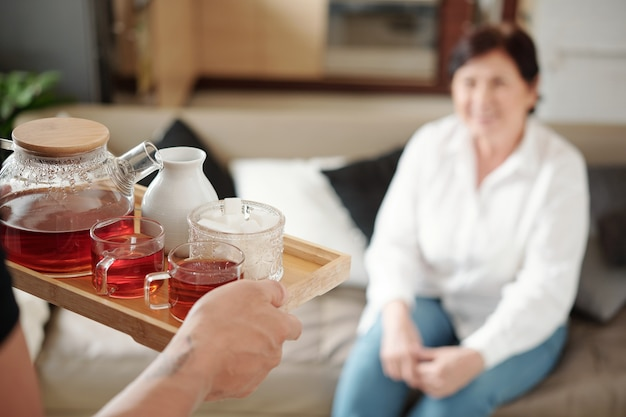 Close-up of son holding tray with teapot and cups and serving it for his mother while she sitting on sofa in the room