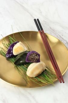 초콜릿과 견과류 필링으로 송편을 닫습니다. 송편은 추석에 쌀가루로 만든 한국의 전통 반달 모양의 떡입니다. 솔잎과 함께 금판에 제공