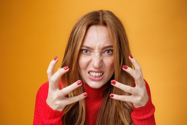 Primo piano di una donna rossa incazzata e arrabbiata che alza le mani e le stringe con rabbia e indignazione irritata e infastidita che fa una smorfia di antipatia, odio e pressione sul muro arancione