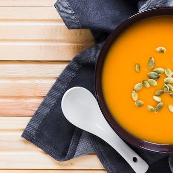 Крупный суп и ложка на полотенце